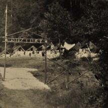 """1946 - 2. oddíl táboří pod hradem Kokořín; táborová brána s nápisem """"Roztoky"""""""